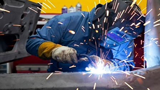 person welding wearing protective helmet, sparks flying