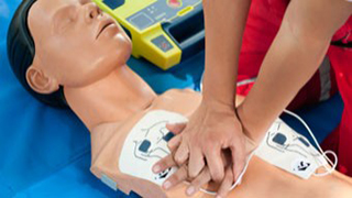 person practicing with CPR dummy